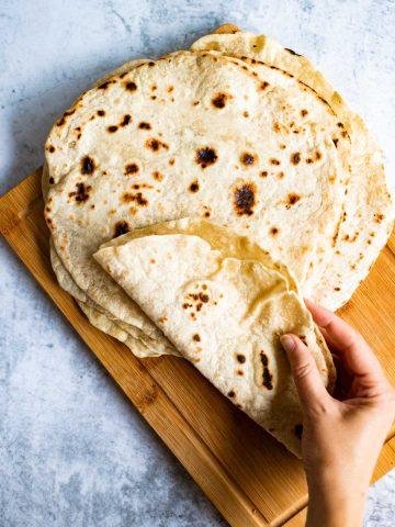 Jamaican roti on a chopping board being folded by a hand to make a vegan wrap