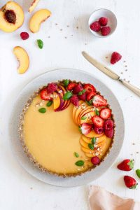 Vegan peach tart with berries and peaches on top
