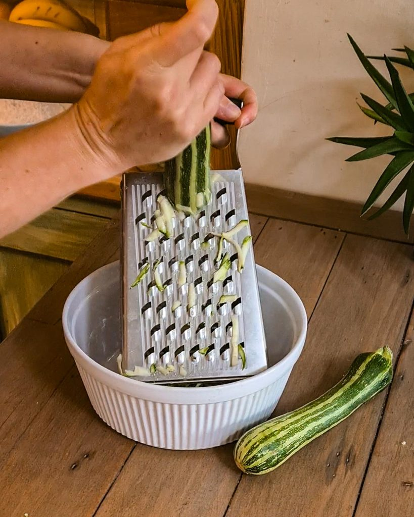 grating zucchini on a grater