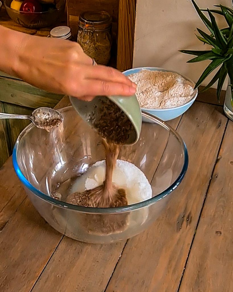 adding linseed egg to a bowl of flour