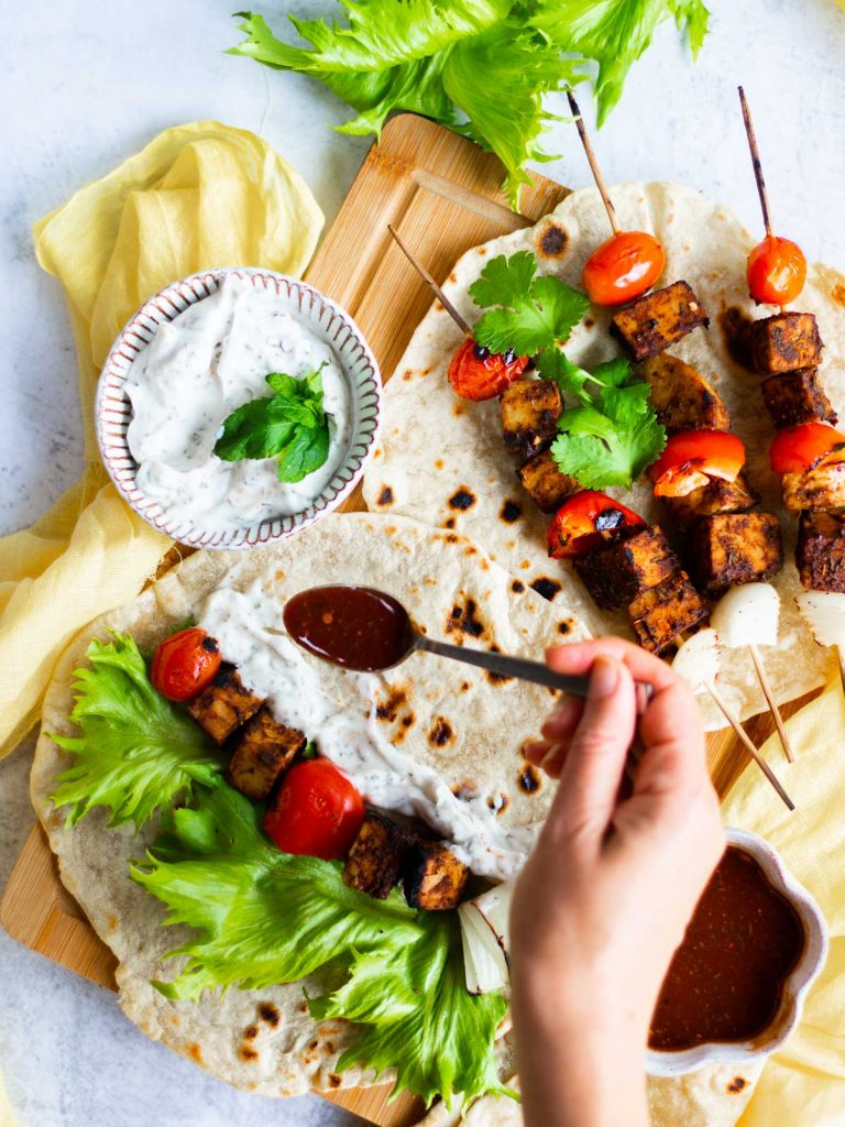 bbq tempeh skewer on a wrap being drizzled with sauce
