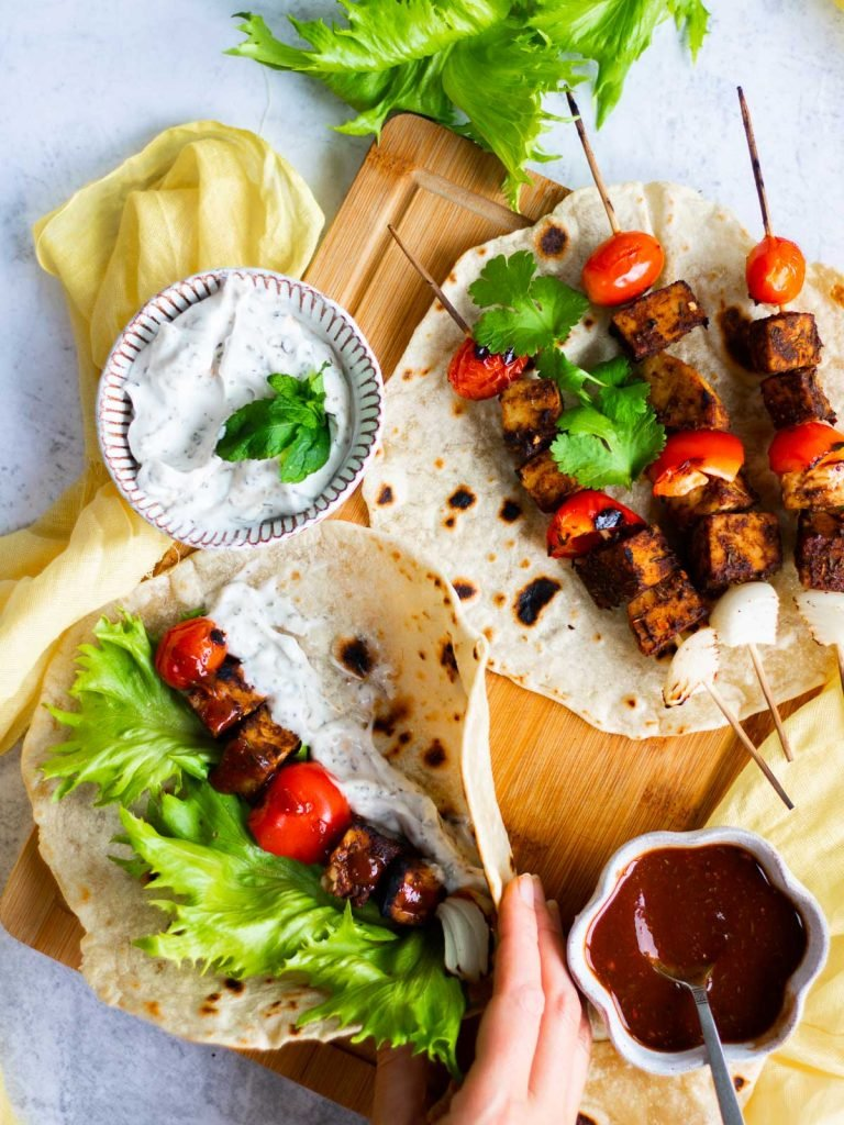 jerk tempeh skewers from the barbeque on a wrap being held by a hand