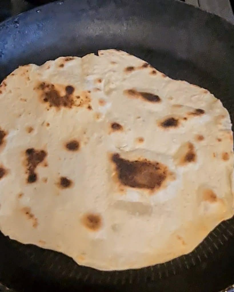 flipping the roti over in the frying pan