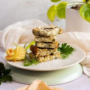 Squares of zucchini slice piled up on a plate with some herbs around it.