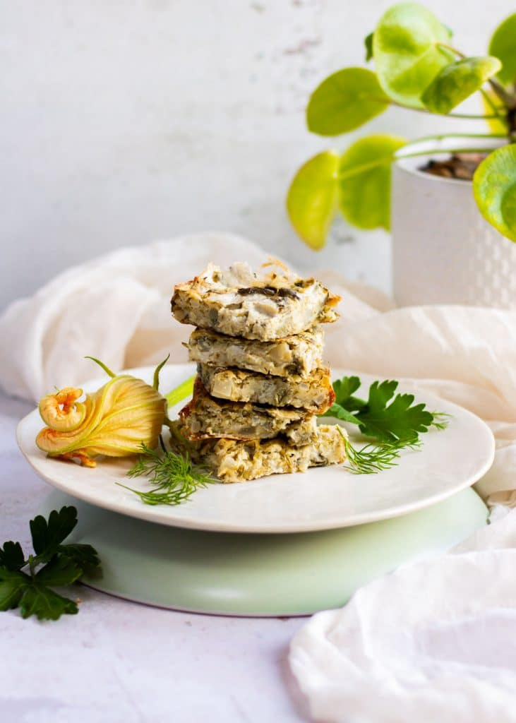Stack of zucchini slices. There is a zucchini blossom behind the plate.