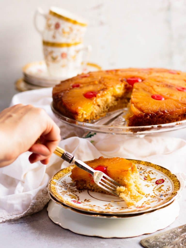 A hand reaching in with a fork, taking a bite of the cake on a plate.