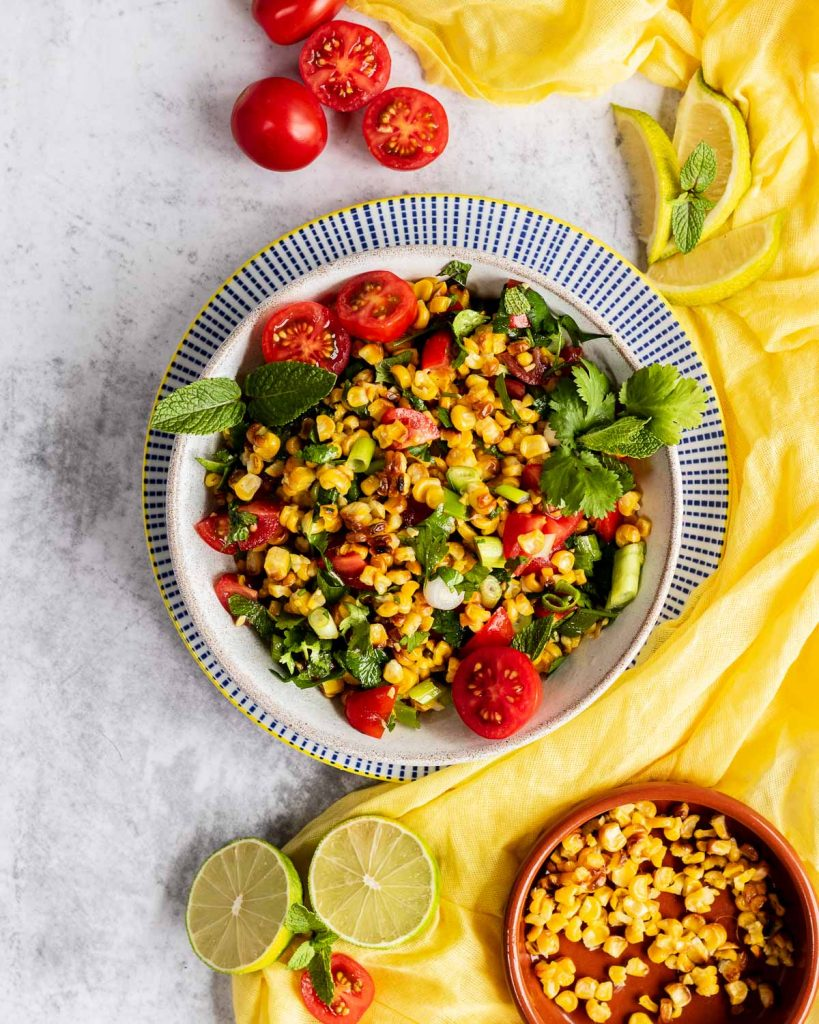 A bowl filled with grilled corn and tomato salad with lots of herbs.