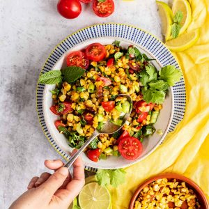 Grilled, roasted corn salad in a bowl with a hand reaching in with a spoon to scoop some up.