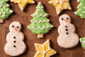sugar cookies decorated as snowmen and christmas trees