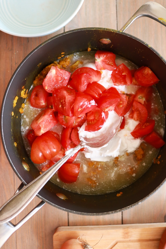 adding the tomatoes to the dhal