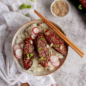 A bowl of japanese rice with miso aubergine laid on top. There are sesame seeds, radish and spring onions to garnish.
